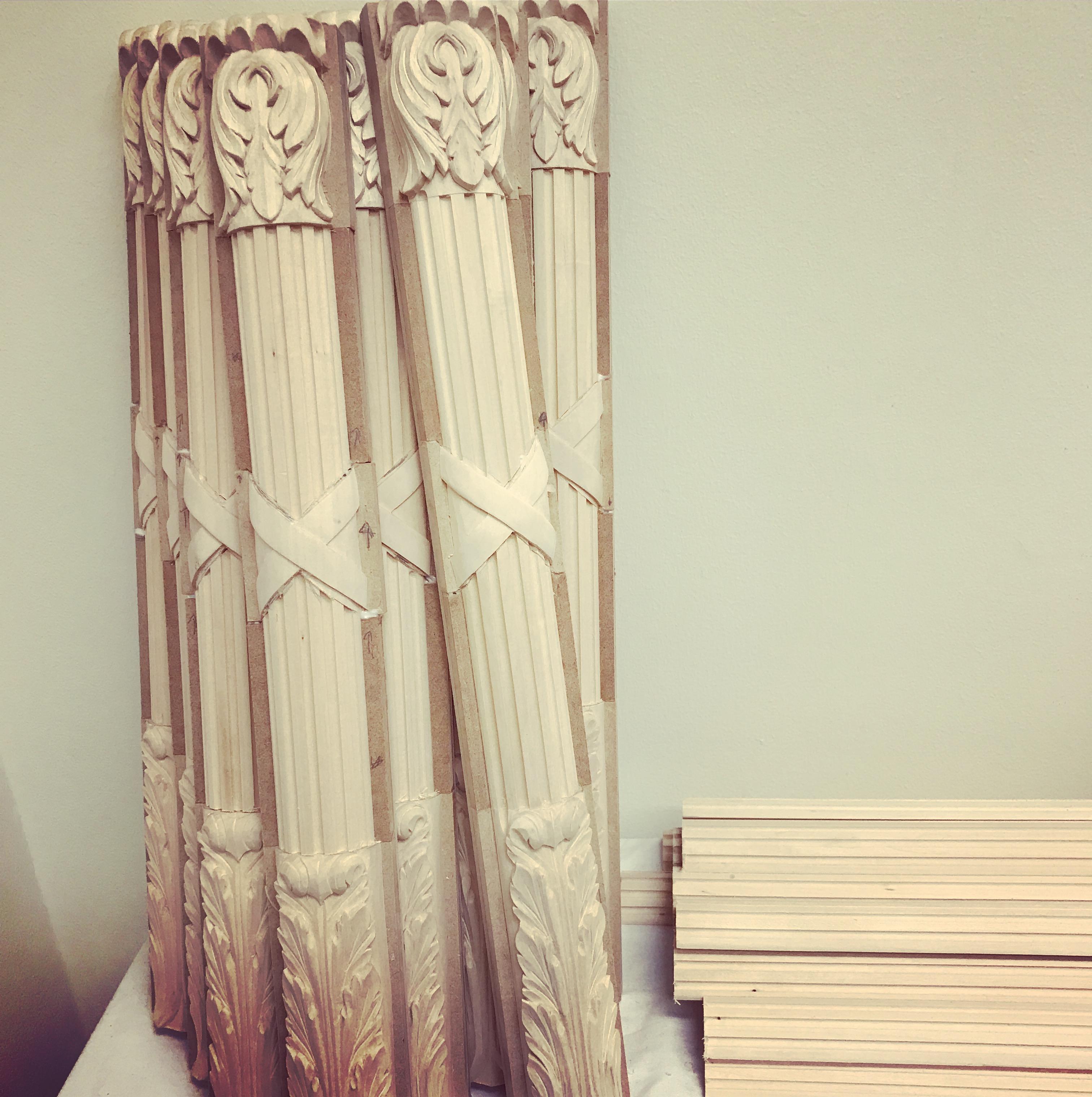 Vackert snidade träåpilastrar lutade mot en vägg i en verkstad
