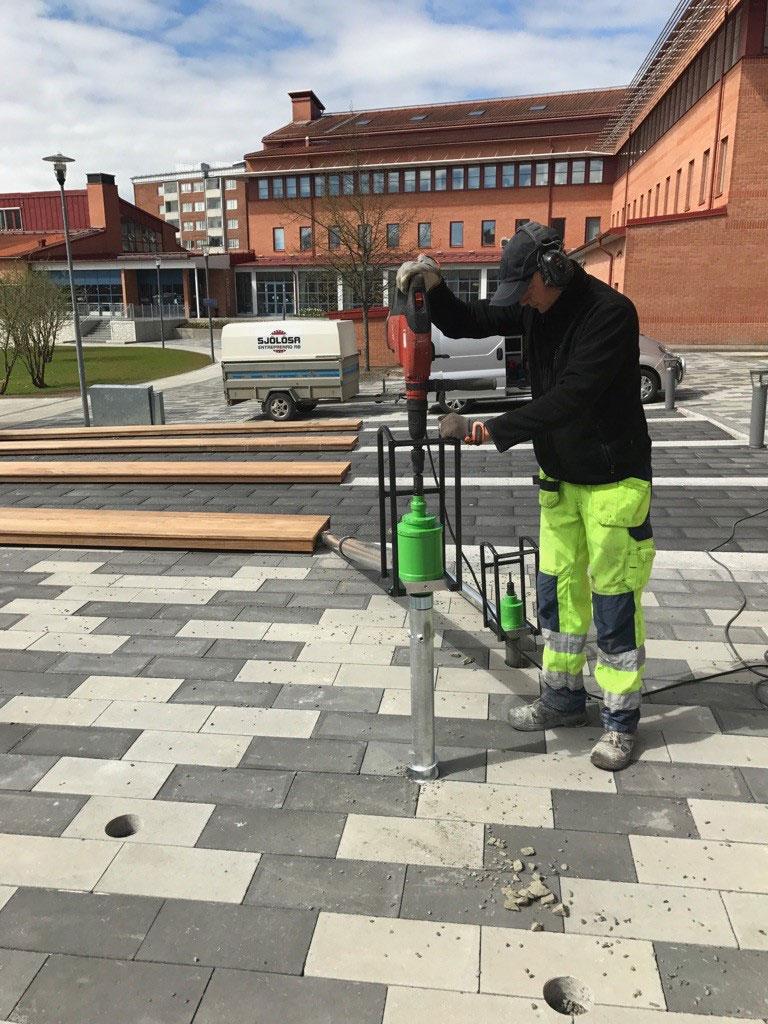 Anläggningsprfofset peter skruvar ner en Stavrex markskruv genom marksten vid Högskolan i Skövde
