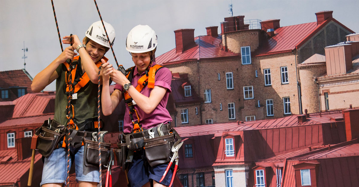 Två ungdomar med fallskyddsutrustning på en takkuliss under Yrkes-SM 2016