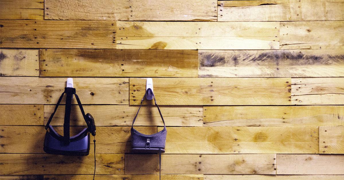 Två virtual reality glasögon upphängda på en grov trävägg