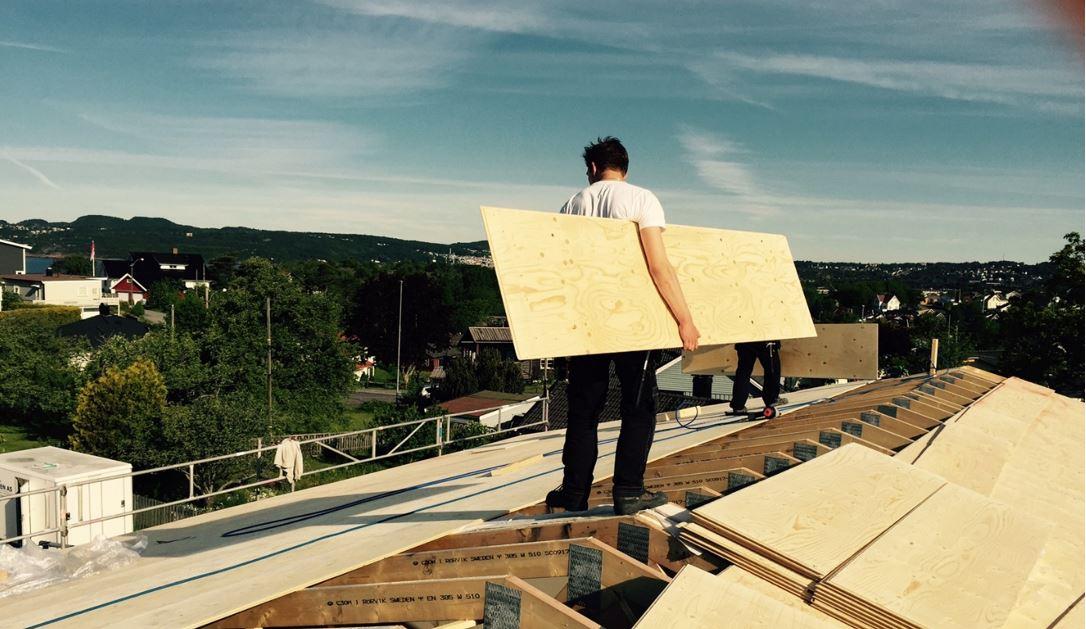 En byggare går på ett tak med en plywoodskiva under armen